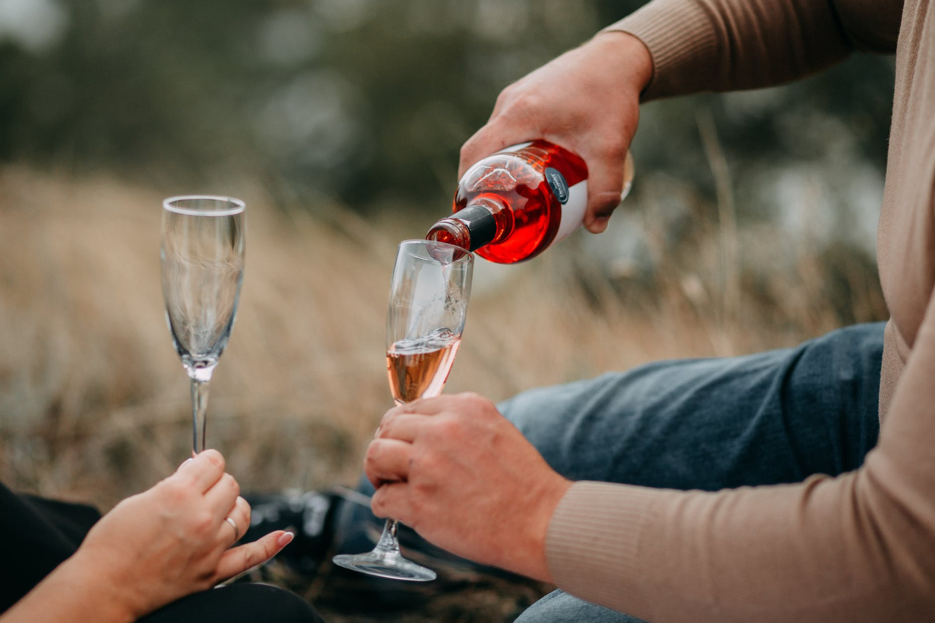 person pouring champagne in champagne flute