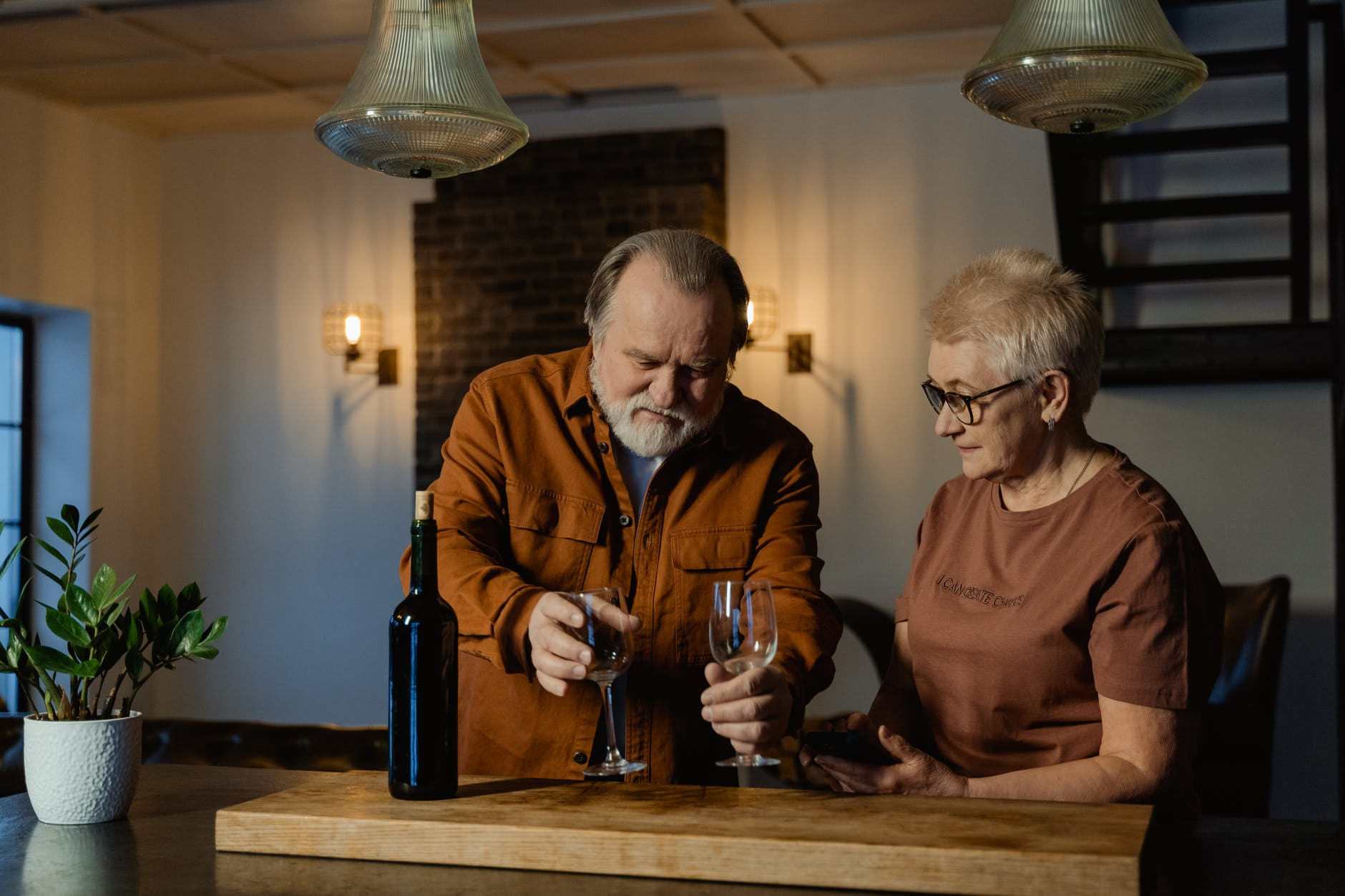 man in brown long sleeve shirt holding wine glasses